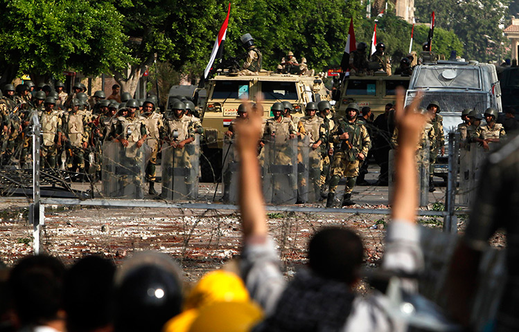 Army soldiers stand guard near the Republican Guard headquarters in Cairo