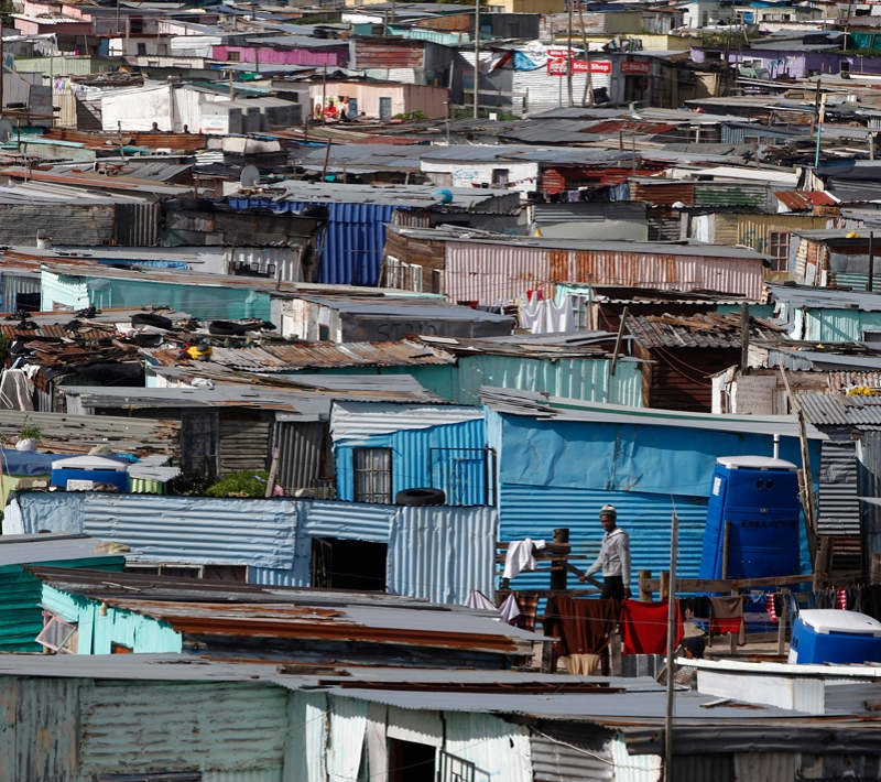 Residents walk through shacks in Cape Town's crime-ridden Khayelitsha township in this picture taken July 9, 2012. At least 11 people have died at the hands of vigilantes in the township since January as angry residents, tired of poor policing, take the law into their own hands. Picture taken July 9, 2012. To match Feature SAFRICA-CRIME/ REUTERS/Mike Hutchings (SOUTH AFRICA - Tags: CRIME LAW) - RTR34VDA