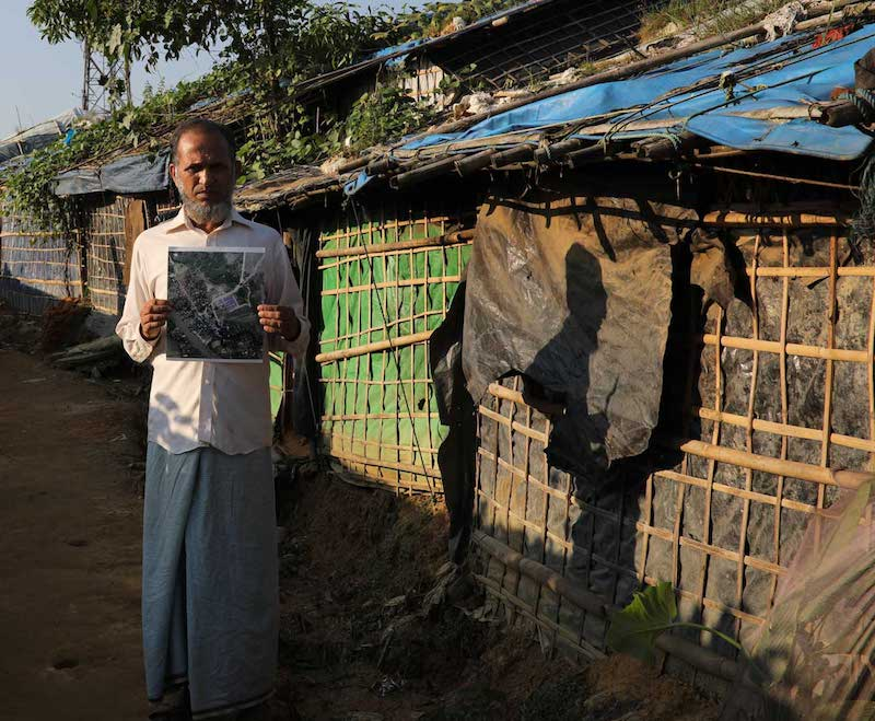 refugee in kutupalong camp with satellite picture of his old e village