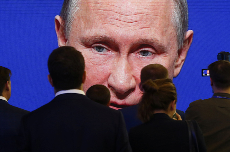 FILE PHOTO: Participants of the St. Petersburg International Economic Forum gather near an electronic screen showing Russian President Putin during a session of the forum in St. Petersburg